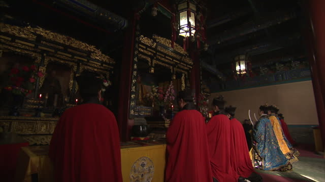 Priests kneel at an altar in the Bai Yun Guan Temple, Beijing.
