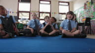 LA Primary school students sitting on classroom floor eagerly raising their hands / Great Yarmouth, England, United Kingdom