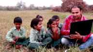 Primary School Students with Teacher In Class Using Laptops outdoor