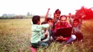 Scuola elementare studenti e insegnante seduto nel campo con computer portatile