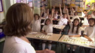 Primary school teacher pointing to chalkboard as children raise their hands to answer question / calling on child who answers question