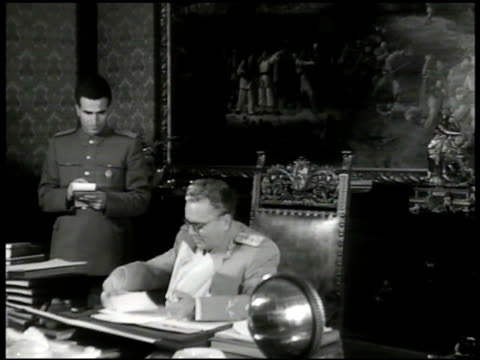 Prime Minister Josip Broz Tito at desk w/ male assistant looking at papers VS Tito at desk looking at paper work Communist Tito's Villa