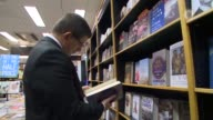 Prime Minister of Turkey Ahmet Davutoglu looks at a book at the Waterstones book store in London England on January 18 2016