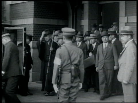 Prime Minister Saionji Kinmochi in top hat leading large crowd at railroad train station walking out of bulding into waiting car getting out of car