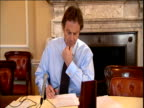 Prime Minister Tony Blair sits at desk inside No 10 Downing Street looking closely at paperwork London Dec 00
