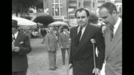 Prince Aly Khan passes walking on crutches as he talks with a man on the grounds of the DeauvilleLa Touques Racecourse where the Grand Prix de...