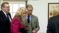 Prince Charles and Camilla visit Speyside Cooperage Charles and Camilla sitting on sofa in cafe area in front of Burntisland Whisky poster on wall...