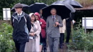 Prince Charles at Swansea Community Farm WALES Swansea EXT Prince Charles Prince of Wales chatting with others holding umbrellas then along in...