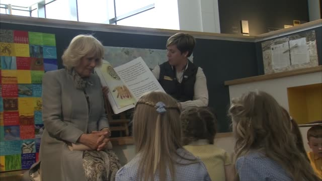Prince Charles Camilla Duchess of Cambridge visit to Seamus Heaney HomePlace Camilla sitting with children listening to story / Charles watching...