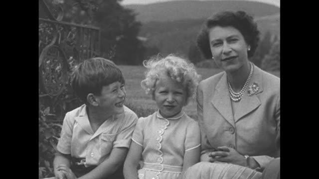 Prince Charles Princess Anne and Queen Elizabeth II smile for the camera pan Philip Duke of Edinburgh smiles next to them Balmoral Castle stands in...