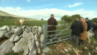 Prince Charles visits the Burren Charles chatting with men in field / Charles inspects livestock / SOME SCROLLING / Charles along up rocky crag and...