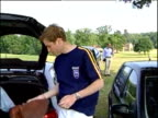 Prince Harry sits in boot of car cleaning polo boots as Prince William puts on boots at polo match England 2000's