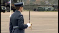 Prince Harry visits RAF Honington Clergyman speaking at microphone SOT faint audio / people in crowd / Harry presenting flag to troop / soldier along...