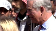 Prince of Wales visits Syrian refugee camp on Jordanian border Royal arrival and tour of camp EXT Prince Charles and Camilla from building and along...