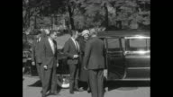 Prince Rainier assists Grace Kelly out of car greeted by White House staff / press photographers / they pose before entering / press follows them to...