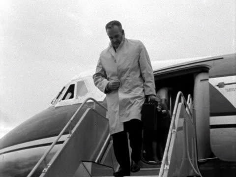 Prince Rainier of Monaco leaves a plane at London Airport and smiles at photographers 1961