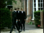 Prince William walks along road with class mates in Eton College uniform Berkshire 1990's