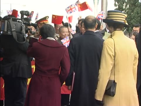 Princess Anne stands waiting in the background as chinese leader Hu Jintao greets flag waving supporters at Heathrow's VIP suite at the start of...