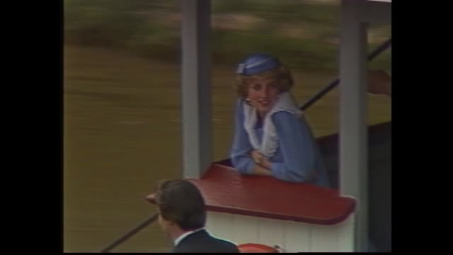 Princess Diana on Murray River cruise– leans on wheelhouse railing of paddle steamer – wearing pale blue dress with sailor style collar and pillbox...