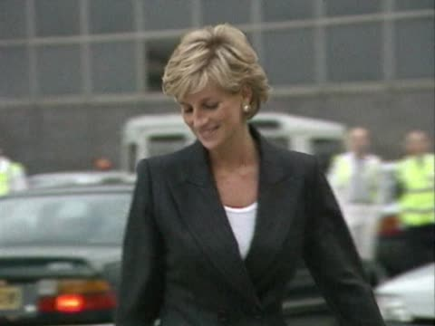 Princess Diana wearing dark business suit walks out of car and into airport service door ready for flight to New York
