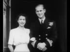 Princess Elizabeth and Prince Philip of Greece stand arm in arm on balcony at Buckingham Palace / CU their arms intertwined with engagement ring on...