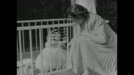 Princess Elizabeth kneels next to baby Prince Charles in playpen and they both play with tiny abacus on railing / different angle of Charles and...