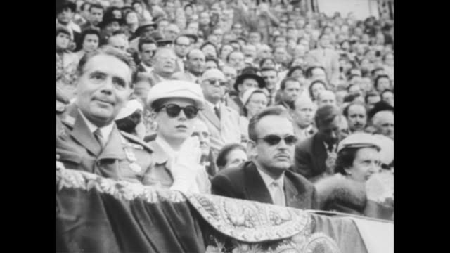 Princess Grace Kelly and Prince Rainier attend bullfight in Majorca in their honor during honeymoon / seated royals applaud as show begins / Kelly...