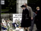 Royal family INSERT C4N SCOTLAND Balmoral Queen Elizabeth II wearing black hat and coat looking at flowers laid outside entrance to estate with...
