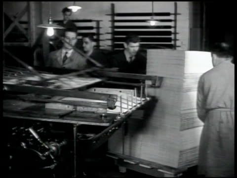 Printing press printing encyclical from Pope Pius XII Men in printing room moving large stack of papers on cart CU Type face for printing press in...