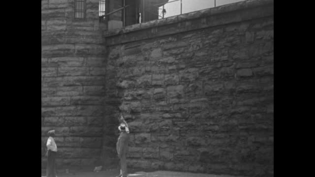 Prison building / Warden Kirk Prather standing at base of stone wall pointing while showing how convicts escaped maybe guard standing nearby /...