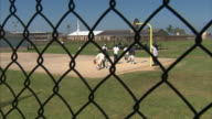 ANGOLA HD *Prison chain link fence in silhouette FG WS Male prisoners playing basketball outside on prison yard court Incarceration correctional...