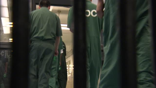 Prison inmates walk single file through a doorway.