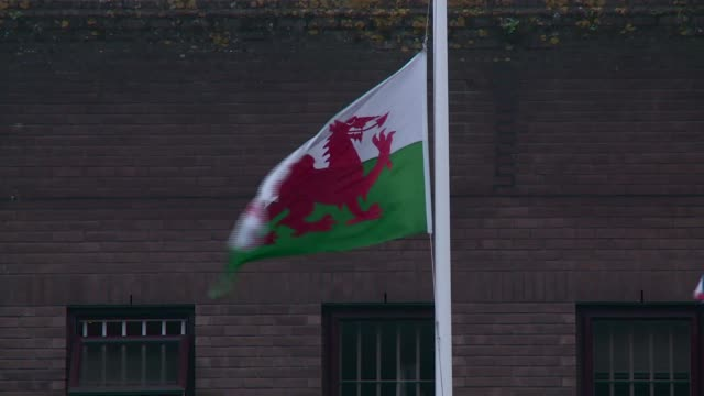 Prison officers protest over worsening conditions WALES Cardiff EXT PAN prison officers standing outside prison building Welsh flag flying on pole...