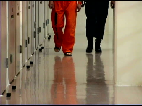 Prisoner and officer walking in prison
