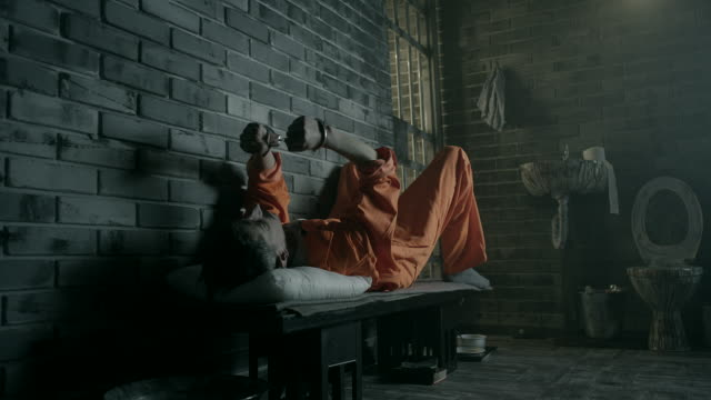 A prisoner lying on his bed in a prison cell