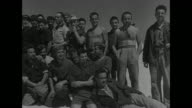 WS prisoner of war camp in desert with Italian naval prisoners / group of prisoners tents in bag / pan of prisoners / CU pan Italian sailor others...