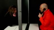 Prigioniero parla ai visitatori al telefono a vetro