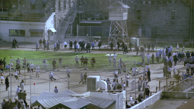 HA WS Prisoners walking and playing ball in prison yard at Folsom State Prison / Folsom, California, USA