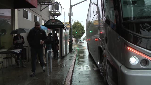 Private bus coaches pick up high tech workers in Latino Mission District in rain for transport to Google campus and other high tech companies