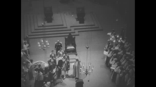 Procession walks down aisle of Westminster Abbey / Queen Elizabeth looks on from Chair of Estate while behind and above her Queen Mary Princess...