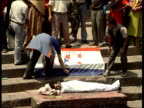 curfew in Kathmandu / body of protester killed by police Body of man lying on steps of building wrapped in white sheet man placing flag on steps...
