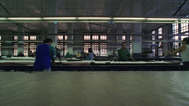 WS Production line in garment factory, workers rolling out fabric