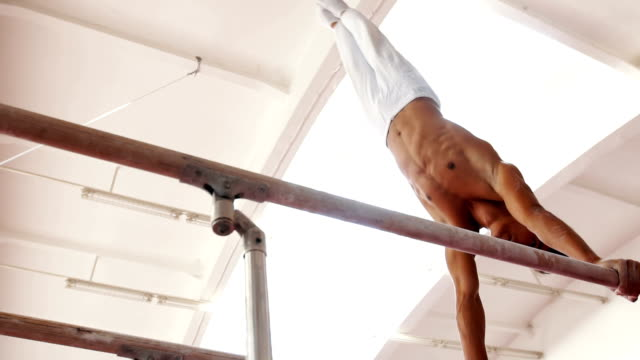 Professional athlete on a parallel bars