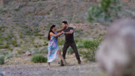 SLO MO. Professional ballroom dancers perform choreographed routine in rocky desert landscape.