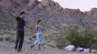 Professional ballroom dancers perform elegant choreographed routine in barren desert setting.