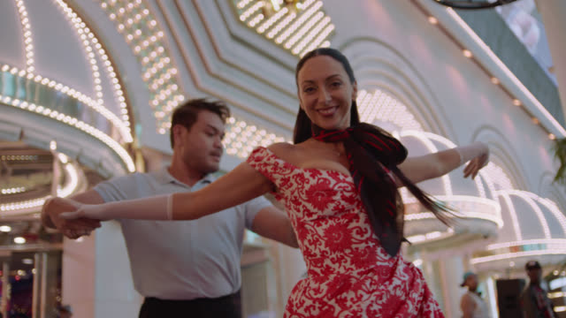Professional ballroom dancers swing and dance outside of Las Vegas casino and smile at camera.