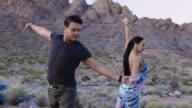 Professional ballroom dancers twirl and strike dramatic pose in scenic desert landscape.