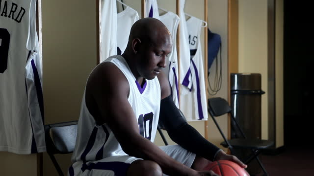 CU professional basketball player in locker room holding basketball preparing for game / Washington, USA