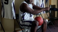 CU PAN professional basketball player in locker room pulling on sleeve preparing for game / Washington, USA