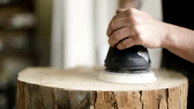 Professional Carpenter grinds Wood In Workshop